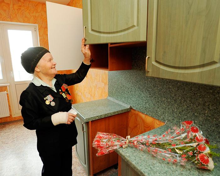 Ветеран боевых действий рассматривает кухню в новой квартире